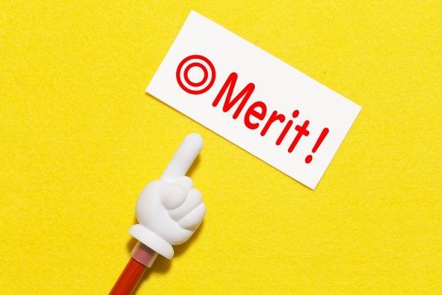 白い紙に書かれた「メリット」と指さし棒