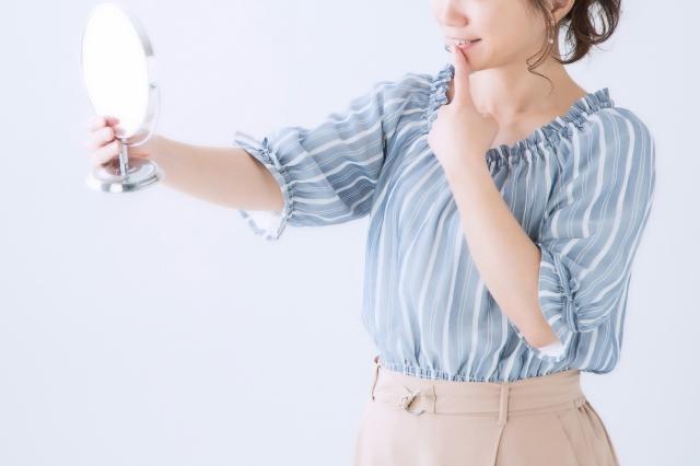 鏡で自身の口元を確認する女性